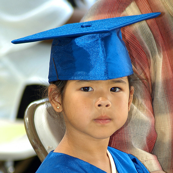 Young girl in blue cap and gown waiting to graduate kindergarten.