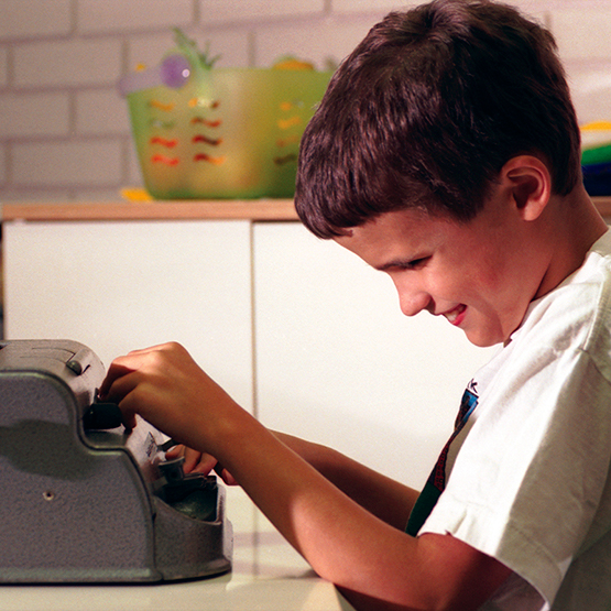 School age boy at a Braille typewriter.
