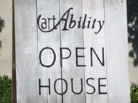 A large wooden sign outside with the artAbility logo on it