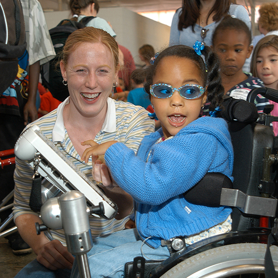 Young girl in a wheelchair accompanied by an aide, and equipped with an assistive technology device.