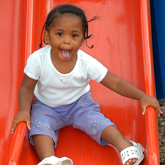 Young girl laughing while sliding down a playground slide.
