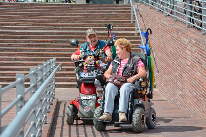 A man and woman riding scooters up a series of ramps.