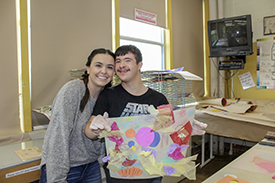 A CDHD student trainee next to an art Ability participant holding up his artwork.