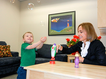 Dr. Gwen Mitchell using a bubble machine with a young child at the Child and Youth Study Center.