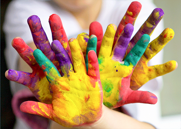 Children's hands covered in multi-colored finger paint.